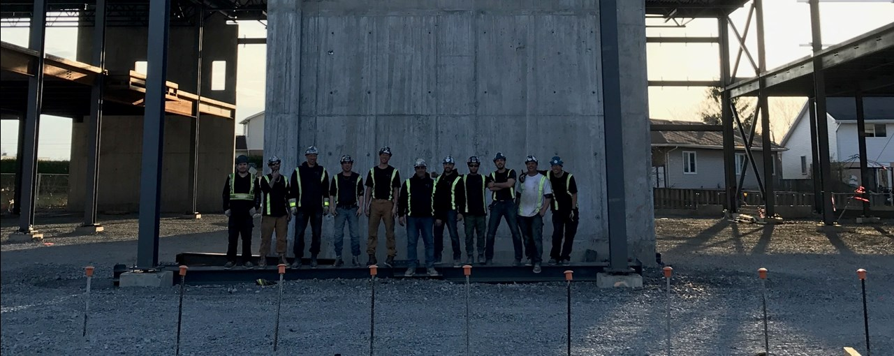 Workers posing in front of an incomplete building